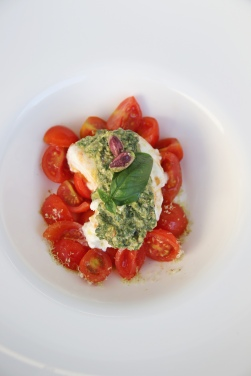 Burrata with tomatoes and arugula and pistachio pesto.