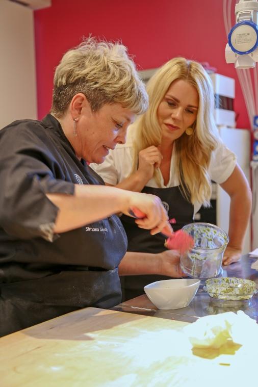 Simone teaching me to make her arugula pesto.